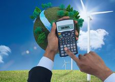 Digital composite image of hands using calculator with planet earth and windmills on grassy field ag. Digital composite of Digital composite image of hands using Stock Photography
