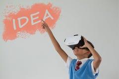 Composite image of digital composite image of idea text on black spray paint. Digital composite image of idea text on black spray paint against schoolboy using Stock Photo