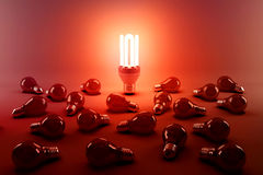 Digital composite image of illuminated energy efficient lightbulb by bulbs. On gray background royalty free illustration