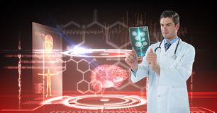 Digital composite image of male doctor looking at x-ray with interface graphics in background stock image