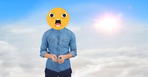 Digital composite image of man using phone face covered with emoji against sky Stock Image