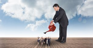Digital composite image of manager watering executives on boardwalk Stock Photo