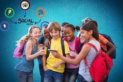 Digital composite image of school students looking at smart phone with various icons against blue ba. Digital composite of Digital composite image of school Royalty Free Stock Image