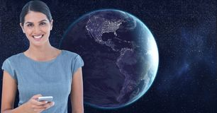 Digital composite image of smiling beautiful woman with cell phone in space standing against earth. Digital composite of Digital composite image of smiling Stock Photos
