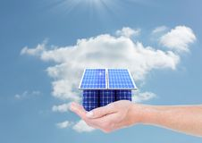 Digital composite image of solar panel house on hand against sky Stock Photography
