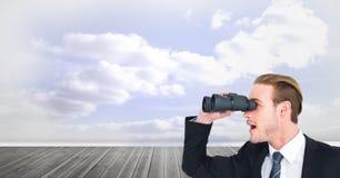 Digital composite image of surprised businessman using binoculars against cloudy sky. Digital composite of Digital composite image of surprised businessman using Royalty Free Stock Image