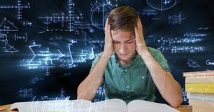 Digital composite image of tensed male student against blackboard with equations Stock Photo