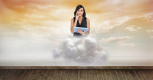 Digital composite image of woman holding tablet computer on cloud over floorboard in sky. Digital composite of Digital composite image of woman holding tablet Royalty Free Stock Images