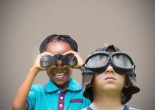 Kids holding binoculars with blank brown background Royalty Free Stock Photo