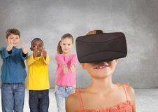 Kids pointing at girl with VR headset in grey room Stock Images