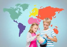 Kids turning world globe in front of colorful world map Royalty Free Stock Images