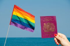 Digital composite of LGBT flag isolated overlooking the ocean with hand holding UK passport. LGBT flag isolated overlooking the ocean Stock Photo
