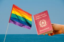 Digital composite of LGBT flag isolated overlooking the ocean with Italian passport in the foreground. LGBT flag isolated overlooking the ocean Royalty Free Stock Photo