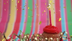Candle on a cupcake and confetti. Digital composite of a lighted candle on a cupcake with a colorful background and gold confetti falling in the screen stock video
