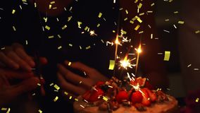 Sparkles on a cake and confetti. Digital composite of lighted sparkles on a birthday cake while gold confetti fall in the screen stock video