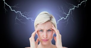 Lightning strikes and stressed woman with headache holding head. Digital composite of Lightning strikes and stressed woman with headache holding head Stock Photo