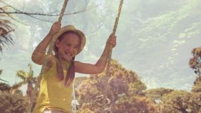 Little girl on a swing. Digital composite of a little Caucasian girl playing on a swing and a forest trail filled with trees stock video