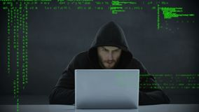 Male hacker using a laptop. Digital composite of a male Caucasian hacker using a laptop while codes appear in the foreground stock footage