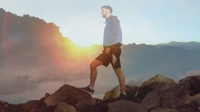 Hiker standing mountain rocks. Digital composite of a male Caucasian hiker standing on rocks on top of mountains at sunset stock video footage