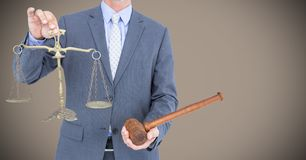 Male judge mid section with gavel and scales against light brown background. Digital composite of Male judge mid section with gavel and scales against light Royalty Free Stock Photo