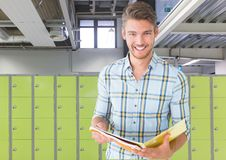 Male student holding book in front of lockers. Digital composite of male student holding book in front of lockers Royalty Free Stock Images