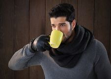 Man against wood with warm scarf and gloves and cup Stock Photo