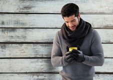 Man against wood with warm scarf and gloves and jumper. Digital composite of Man against wood with warm scarf and gloves and jumper Stock Image
