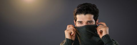 Man hiding under jumper with eyes peering out. Digital composite of Man hiding under jumper with eyes peering out Stock Photo