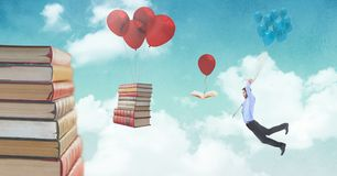 Man holding balloons and floating books on balloons in surreal sky stock image