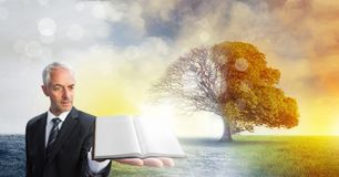 Man holding book with magical surreal seasonal tree imagination. Digital composite of Man holding book with magical surreal seasonal tree imagination Stock Photos