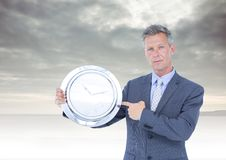 Man holding clock in front of cloudy sky Stock Image