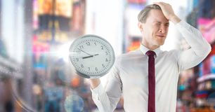 Man holding clock in front of colorful city Stock Photography