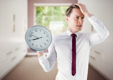 Man holding clock in front of room window Royalty Free Stock Photos
