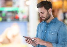 Man holding phone in mall shopping centre Stock Photography