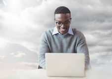 Man on laptop in cloudy sky. Digital composite of Man on laptop in cloudy sky Royalty Free Stock Images