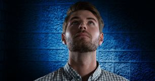 Man looking up with dark blue wall background. Digital composite of Man looking up with dark blue wall background Stock Image