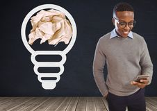 Man on phone standing next to light bulb with crumpled paper ball in front of blackboard. Digital composite of Man on phone standing next to light bulb with Stock Images