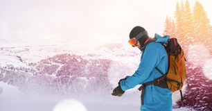 man skiing on slope putting on glove stock images