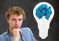 Man standing next to light bulb with crumpled paper ball in front of blackboard. Digital composite of Man standing next to light bulb with crumpled paper ball in Stock Photo