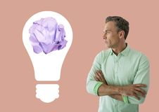 Man standing next to light bulb with crumpled paper ball. Digital composite of Man standing next to light bulb with crumpled paper ball Royalty Free Stock Photos