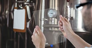 Man taking picture of machinery through transparent device at brewery Royalty Free Stock Image