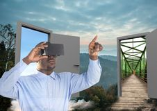 Man with VR glasses in the forest with two doors to go other place. Digital composite of man with VR glasses in the forest with two doors to go other place Royalty Free Stock Photos