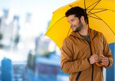 Man with yellow umbrella and blurred blue background Royalty Free Stock Photography
