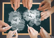 Many Hands writing school subjects on blackboard. Digital composite of Many Hands writing school subjects on blackboard royalty free stock photos