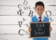 Many letters around Schoolboy holding blackboard with Back to school text Royalty Free Stock Image