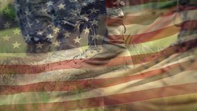 Military boots and American flag. Digital composite of military boots while American flags waving in the background stock footage