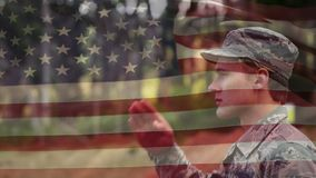 Military man in a park. Digital composite of a military man saluting while in the park and American flag waving in the background stock footage