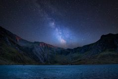 Digital composite Milky Way image of Beautiful landscape image o. Stunning vibrant Milky Way composite image over Beautiful landscape image of Llyn Idwal and stock image