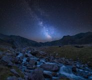 Digital composite Milky Way image of Moody landscape image of ri. Stunning vibrant Milky Way composite image over Landscape image of river flowing down mountain royalty free stock photography