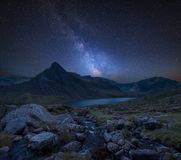 Digital composite Milky Way image of Stunning landscape image of. Stunning vibrant Milky Way composite image over Beautiful landscape image of stream near Llyn royalty free stock photo